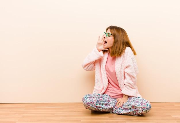 Молодая женщина в пижаме сидит дома громко и сердито кричит, чтобы скопировать пространство сбоку, с рукой рядом с ртом