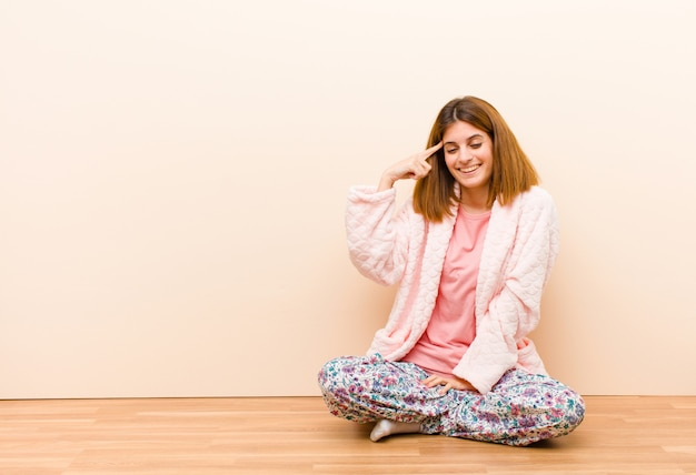 Young woman wearing pajamas sitting at home feeling confused and puzzled, showing you are insane, crazy or out of your mind