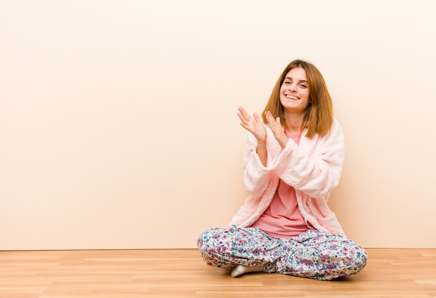 Young woman wearing pajamas sitting at home feeling happy and successful, smiling and clapping hands, saying congratulations with an applause