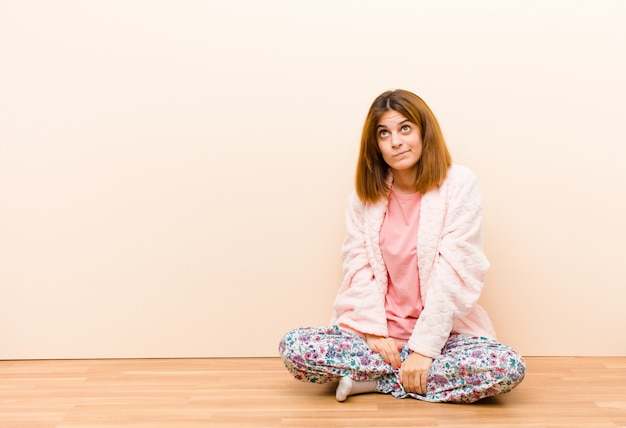 Young woman wearing pajamas sitting at home looking puzzled and confused, wondering or trying to solve a problem or thinking