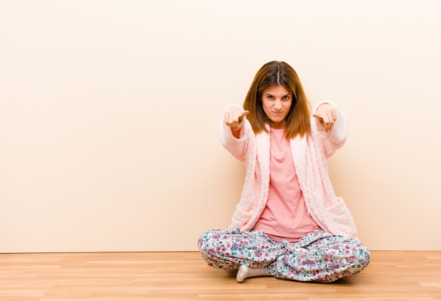 Young woman wearing pajamas sitting at home pointing forward at camera with both fingers and angry expression, telling you to do your duty