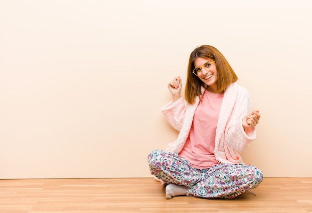 Young woman wearing pajamas sitting at home smiling, feeling carefree, relaxed and happy, dancing and listening to music, having fun at a party