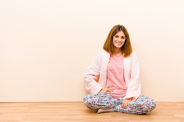 Young woman wearing pajamas sitting at home smiling happily with a hand on hip and confident, positive, proud and friendly attitude