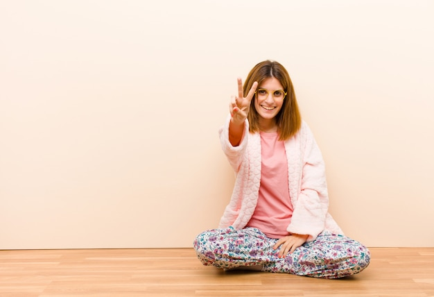 Young woman wearing pajamas sitting at home smiling and looking happy, carefree and positive, gesturing victory or peace with one hand