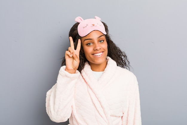 Young woman wearing pajamas and a sleep mask showing victory sign and smiling broadly