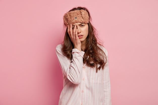 Young woman wearing pajamas and sleep mask