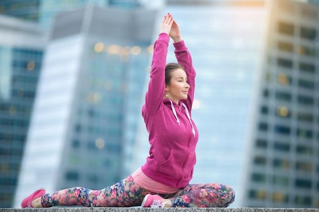 Young woman wearing pink sportswear in king pigeon pose