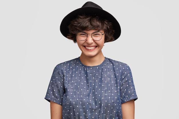 Молодая женщина в блузке в горошек и большой шляпе
