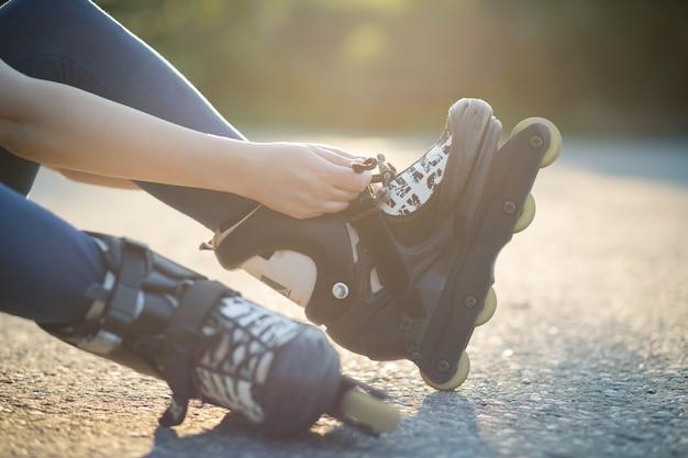 Молодая женщина в костюме готовит роликовые коньки для катания на коньках