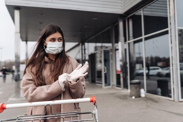 Молодая женщина носить защитную маску против коронавируса 2019-нков, толкая корзину.