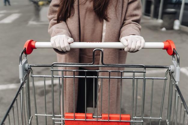 쇼핑 카트를 밀고 코로나 바이러스 2019-ncov에 대 한 보호 얼굴 마스크를 착용하는 젊은 여자.