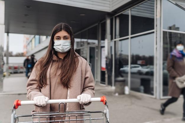쇼핑 카트를 밀고 코로나 바이러스에 대한 보호 얼굴 마스크를 착용하는 젊은 여자.