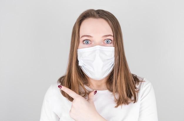 보호 마스크를 착용하는 젊은 여자는 측면까지 손과 손가락으로 가리키는 놀란