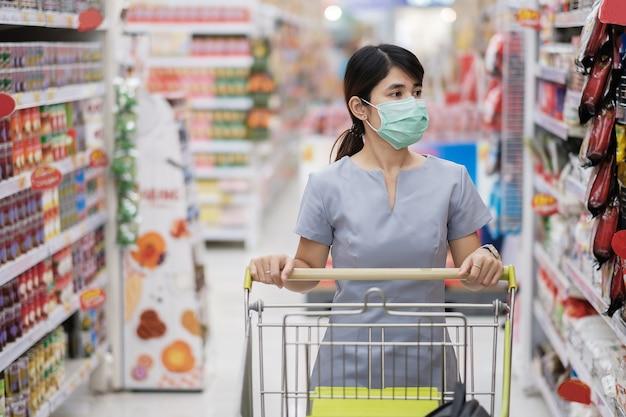 防護マスクを身に着けているとショッピングの若い女性