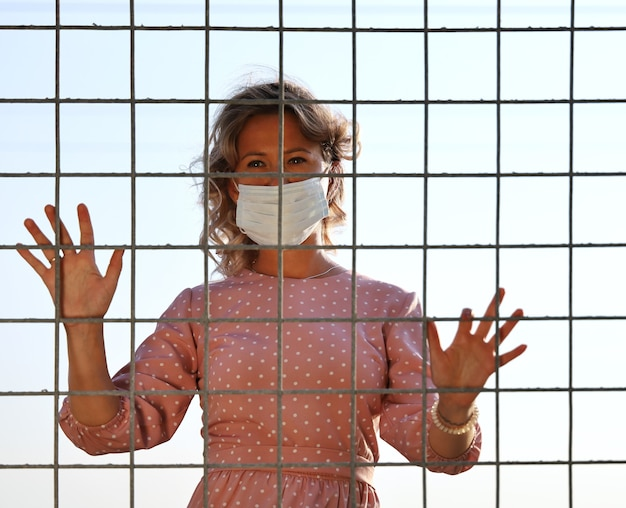 보호용 얼굴 마스크를 쓴 젊은 여성은 선택적인 초점이 있는 사각형 그릴을 들여다본다
