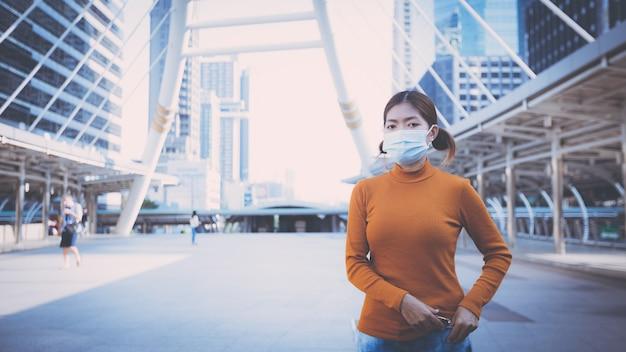 街の通りの屋外で保護フェイスマスクを身に着けている若い女性。ニューノーマル