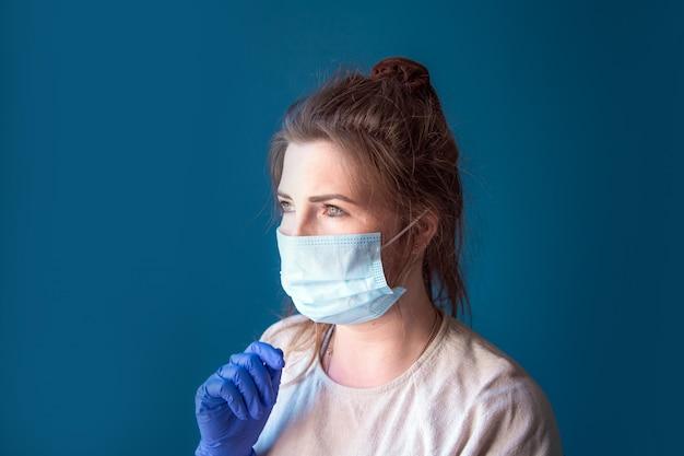 Молодая женщина в защитных перчатках и маске в доме в карантине, выглядит скучно и грустно, для covid-19 coronavirus