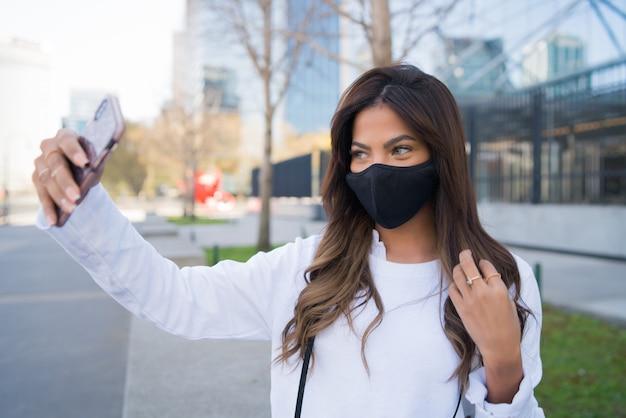 保護マスクを着用し、屋外に立っている間、彼女のmophile電話で自分撮りをしている若い女性。