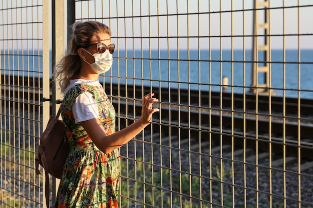 Young woman wearing protective mask looks through the grille at the sun and sea