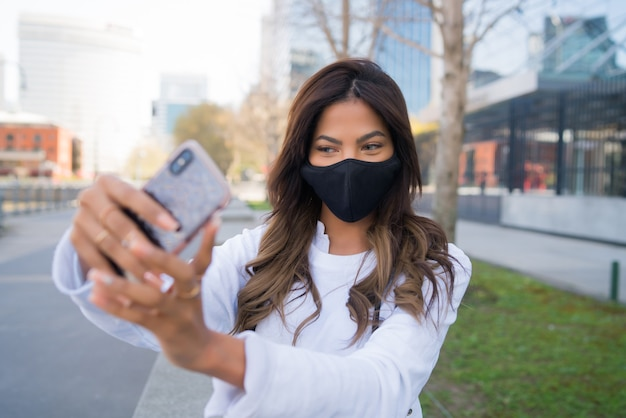 Young woman wearing protective mask and taking selfies with her mophile phone while standing outdoors. urban concept.