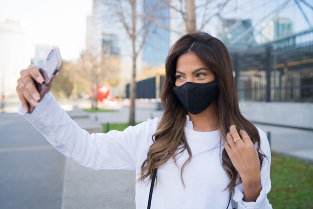 Young woman wearing protective mask and taking selfies with her mophile phone while standing outdoors.
