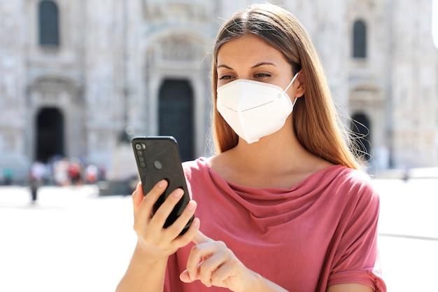 Молодая женщина в защитной маске с помощью приложения для смартфона в милане, италия