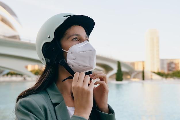 ヘルメットをかぶっている間保護マスクを身に着けている若い女性