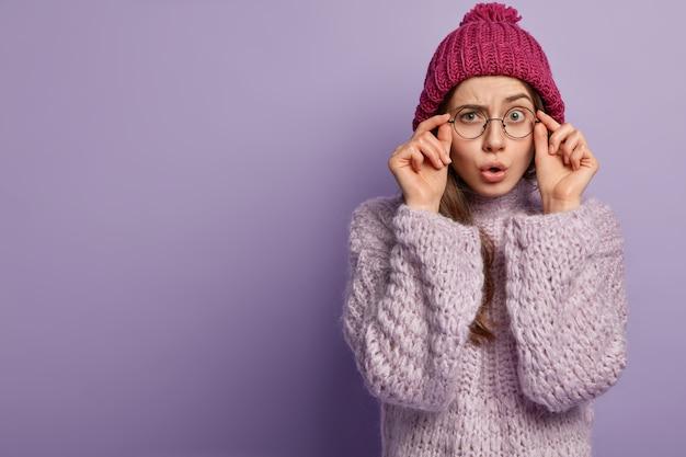 Giovane donna che indossa un maglione viola e cappello