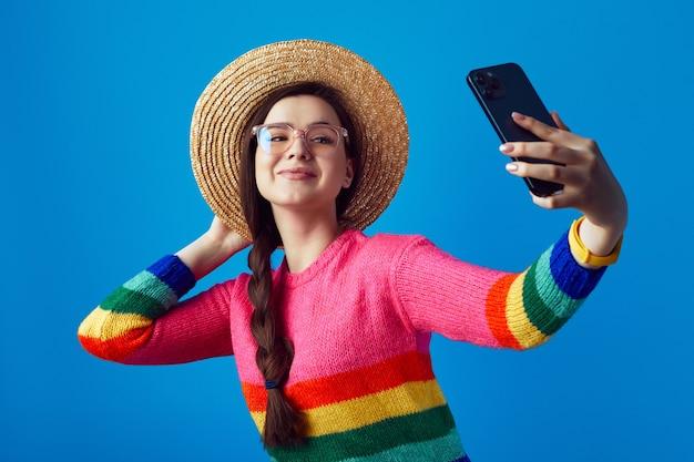 무지개 스웨터와 스마트 폰으로 셀카를 복용 안경을 착용하는 젊은 여자