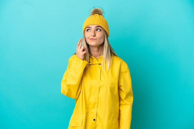 Young woman wearing a rainproof coat over isolated blue background with fingers crossing and wishing the best