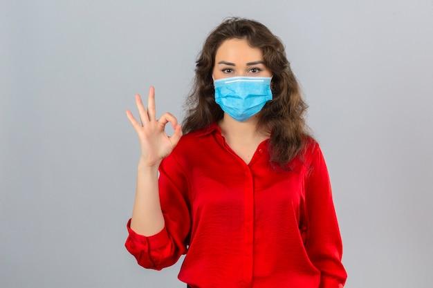 孤立した白い背景の上にokの標識をやって笑顔でカメラを見て医療用防護マスクに赤いブラウスを着た若い女性