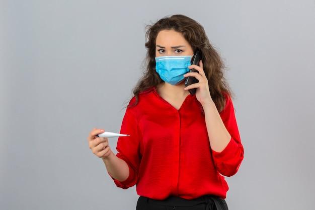 Молодая женщина в красной блузке в медицинской защитной маске разговаривает по мобильному телефону и выглядит обеспокоенной, держа цифровой термометр на изолированном белом фоне