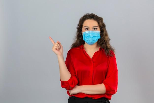 Giovane donna che indossa camicetta rossa nella mascherina protettiva medica che guarda l'obbiettivo con la faccia seria che punta con il dito di lato sopra fondo bianco isolato