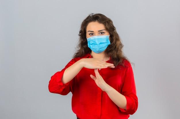 Giovane donna che indossa camicetta rossa in maschera protettiva medica cercando stanchi e annoiati facendo gesto di time out con le mani su sfondo bianco isolato