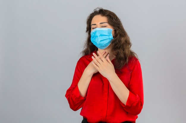 Giovane donna che indossa camicetta rossa in mascherina protettiva medica che sembra malata toccando il suo collo e soffre di mal di gola su sfondo bianco isolato