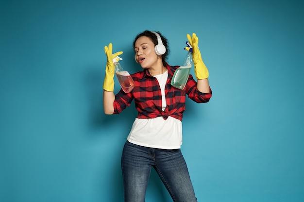 赤い格子縞のシャツとヘッドホンを頭につけたブルージーンズを着た若い女性が歌い、手にスポンジを掃除しながら青でポーズをとる