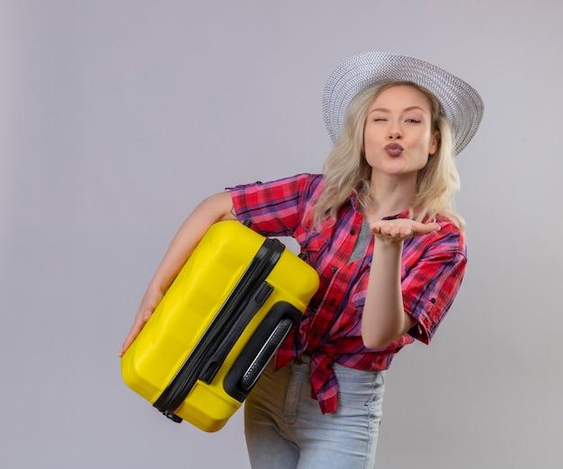 Молодая женщина в красной рубашке в шляпе держит чемодан, показывая жест поцелуя на изолированной белой стене