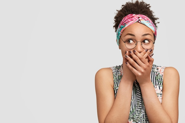 丸い眼鏡とカラフルなバンダナを身に着けている若い女性
