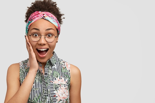 Young woman wearing round eyeglasses and colorful bandana