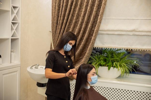 安全マスクを身に着けている若い女性は、保護医療マスクで美容師によって散髪を取得します