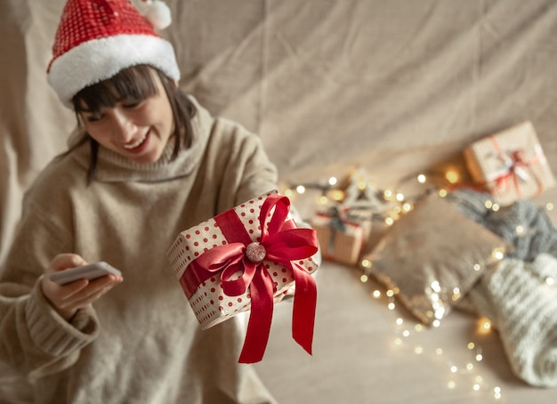 Young woman wearing a santa claus hat holding a beautifully wrapped christmas gift. concept of celebrating christmas during coronavirus pandemic.