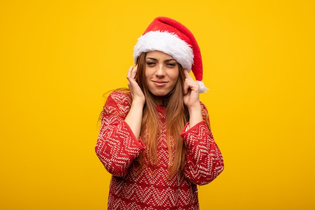 Young woman wearing santa hat covering ears with hands