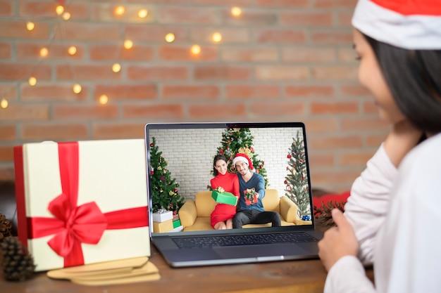 家族とビデオ通話をしているサンタの帽子をかぶって若い女性