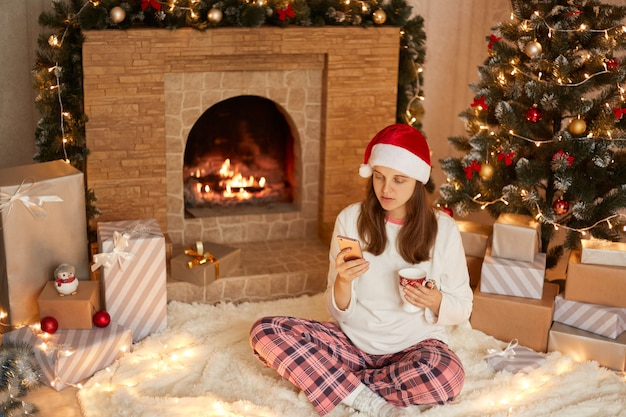 Young woman wearing santa hat and pajamas sitting on floor amongst wrapped christmas presents, fireplace and xmas tree