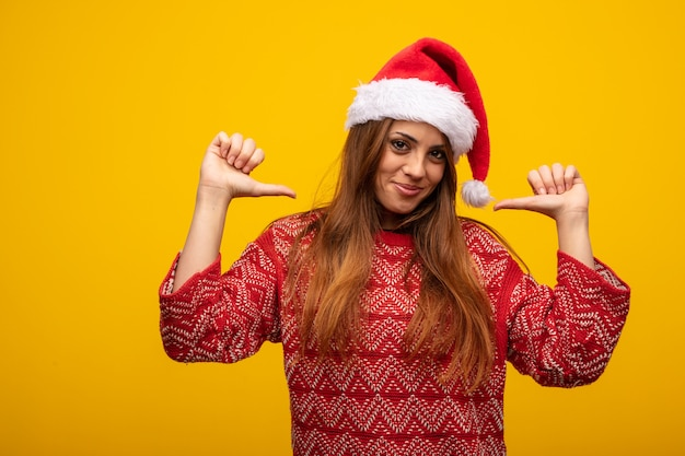 Young woman wearing santa hat pointing fingers, example to follow