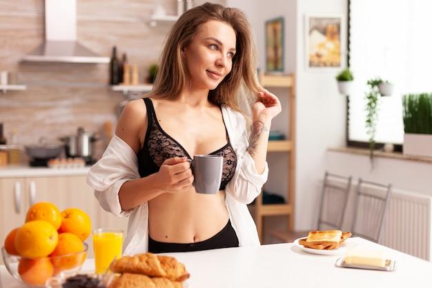 집 부엌에서 아침 식사를 하는 동안 섹시한 란제리를 입은 젊은 여성. 매혹적인 속옷에 문신을 한 매력적인 여성이 웃고 있는 부엌에서 편안한 차 한 잔을 들고 있습니다.
