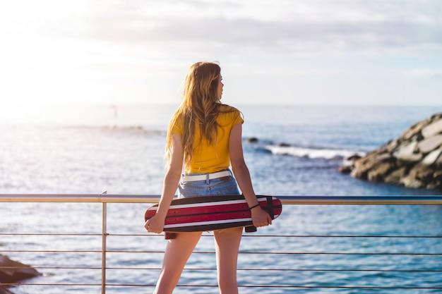 Молодая женщина в шортах смотрит в океан, держа за спиной конек