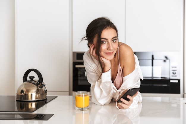 Young woman wearing silk clothing drinking juice in kitchen, and using black cell phone with smile