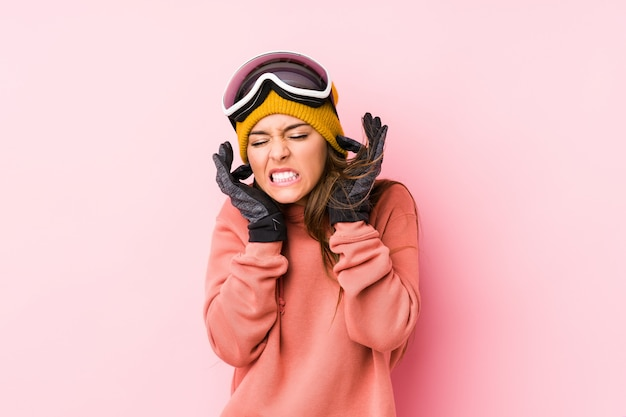 Young woman wearing a ski clothes isolated covering ears with hands.