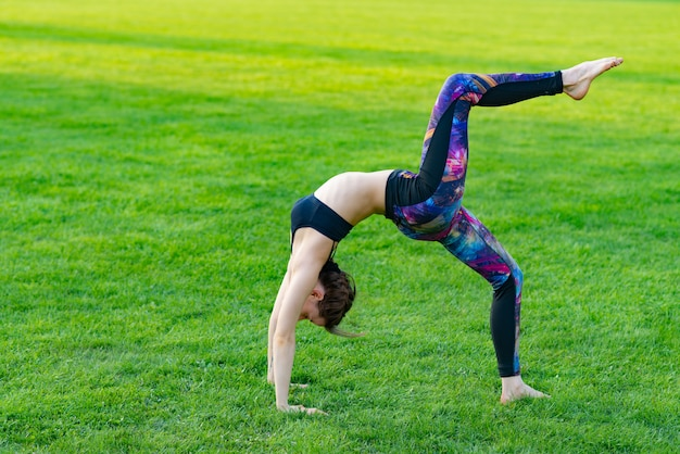Young woman wearing sportswear doing yoga with deflection back